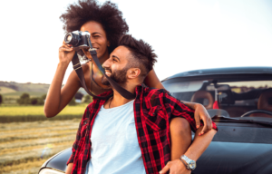 young woman taking photograph of scenery with vintage camera next to young man in plaid shirt; sitting on car